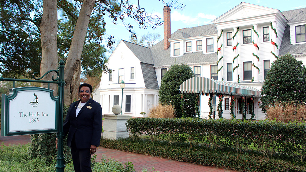 """Alberta Travis poses outside The Holly Inn, which has affectionately been dubbed """"Bert's Place."""""""