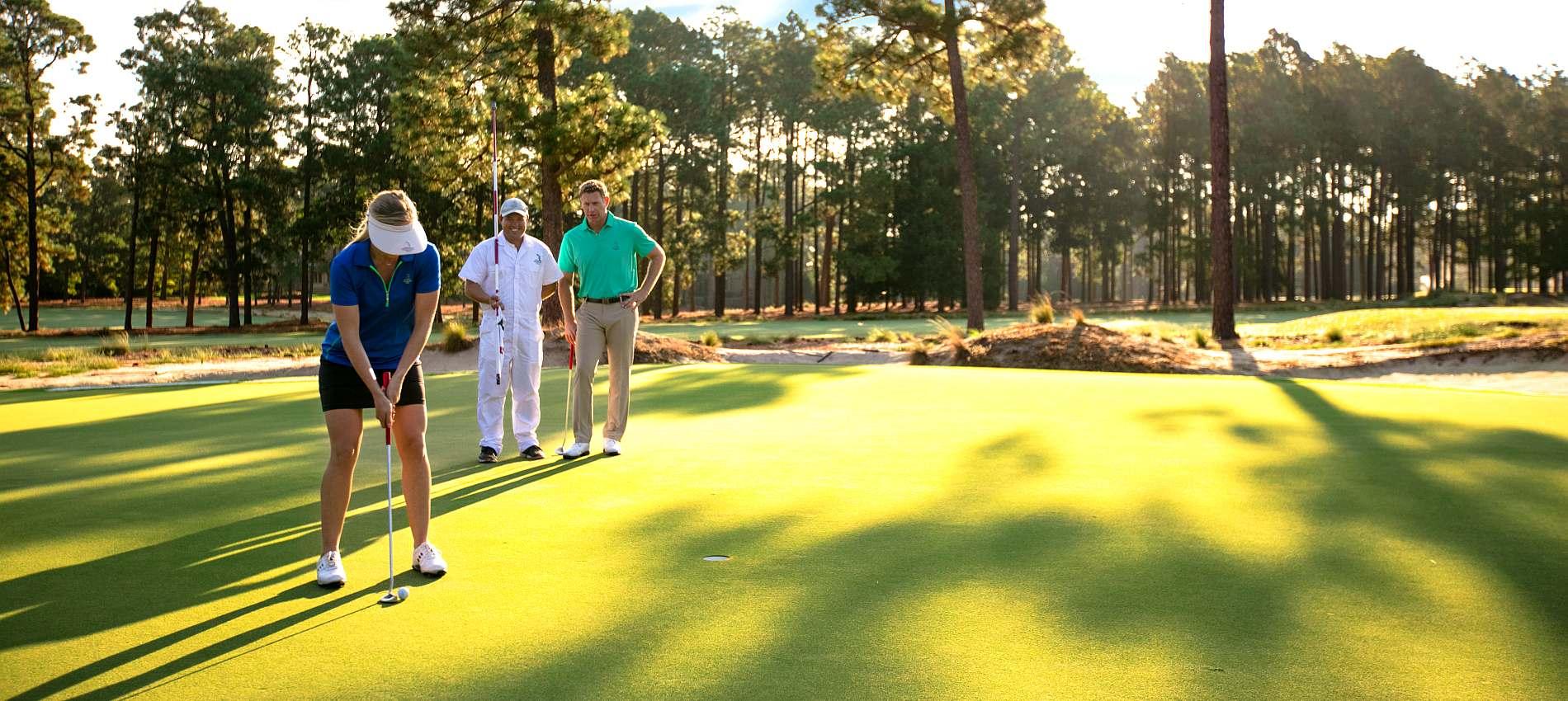 members golfing with caddie
