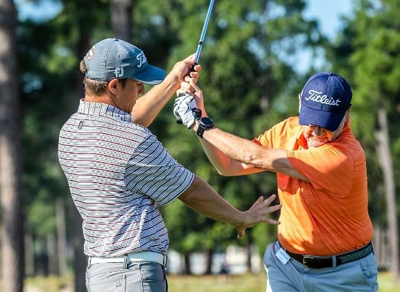 A Pinehurst instructor helping a golfer adjust their swing.